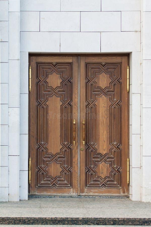 Wide double wooden door in white building. stock photos