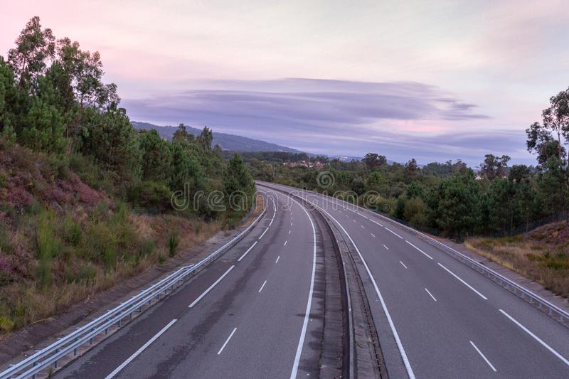 Wide empty highway with curve in the morning. Travel and destination background. Free asphalt road with mountain background. royalty free stock image
