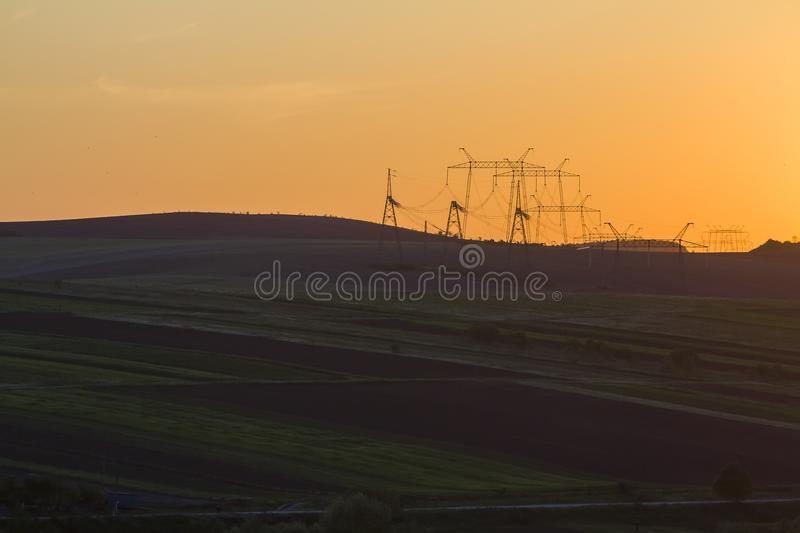 Wide evening panorama of dark plowed and green fields and electrical power line stretching to horizon on beautiful bright yellow. Orange sky at sunset Beauty of royalty free stock photo