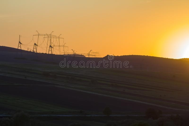 Wide evening panorama of dark plowed and green fields and electrical power line stretching to horizon on beautiful bright yellow o. Range sky at sunset Beauty of royalty free stock photos