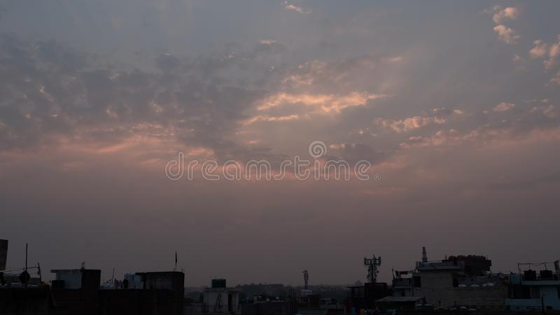 Wide evening sky with a aerial view cityscape. Orange light is poking from the patches of clouds. a beautiful sunset at delhi after a shower of rain stock image