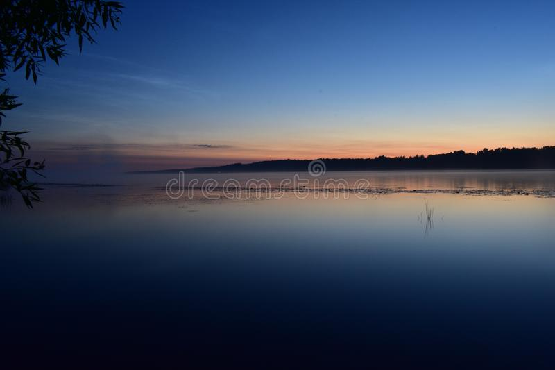 The wide expanse of water in the river the night of the sunset, the branches bent over royalty free stock image