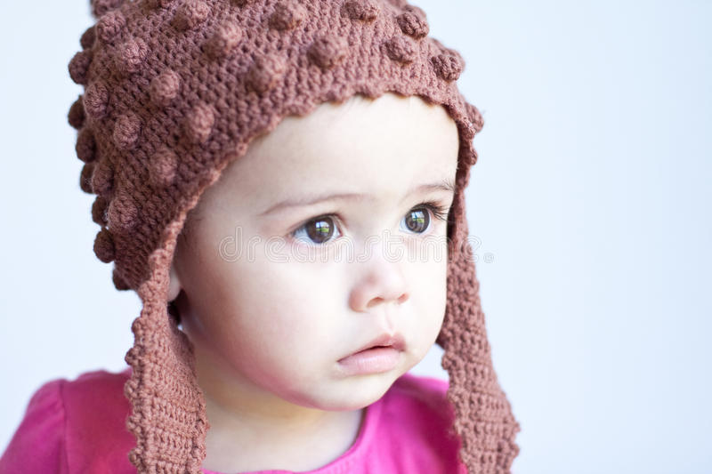 Wide-eyed baby girl's face. A pretty 11-month-old baby has a serious expression on her face. She weas a pink top and brown knitted hat. She's multicultural stock photos