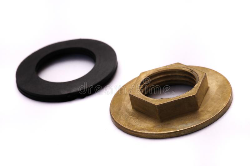 Wide Flange Nut And Gaskets. A photo taken on two gaskets and a brass basin and kitchen tap wide flange nut against a white backdrop. The items are placed side royalty free stock images