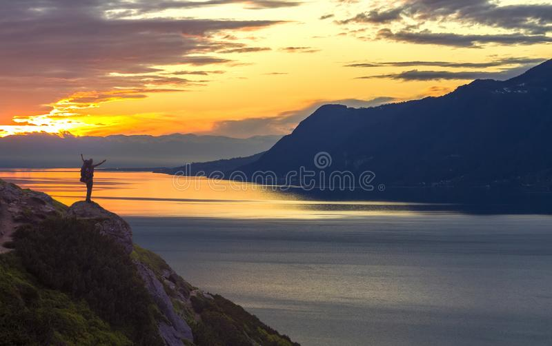 Wide mountain lake panorama. Small silhouette of tourist with backpack on rocky mountain slope with raised hands on lake water royalty free stock photos
