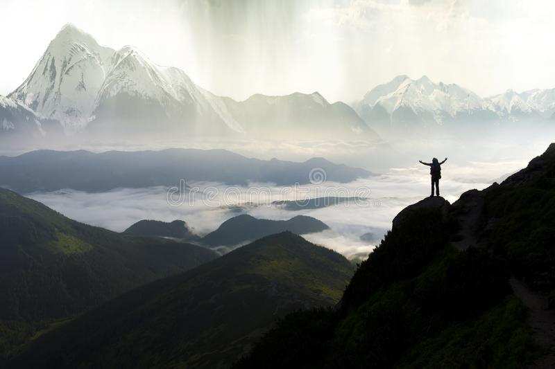 Wide mountain panorama. Small silhouette of tourist with backpack on rocky mountain slope with raised hands over valley covered royalty free stock photos