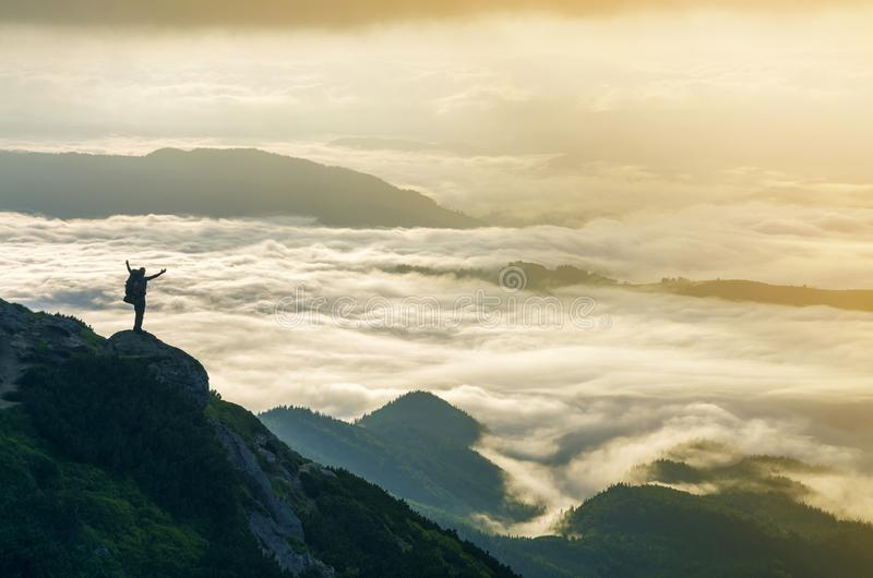 Wide mountain panorama. Small silhouette of tourist with backpack on rocky mountain slope with raised hands over valley covered royalty free stock photo