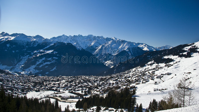 Wide mountains village and sky. View of verbier in the swiss alps on perfect crisp winters day, perspective compression from extreme telephoto lens stock images