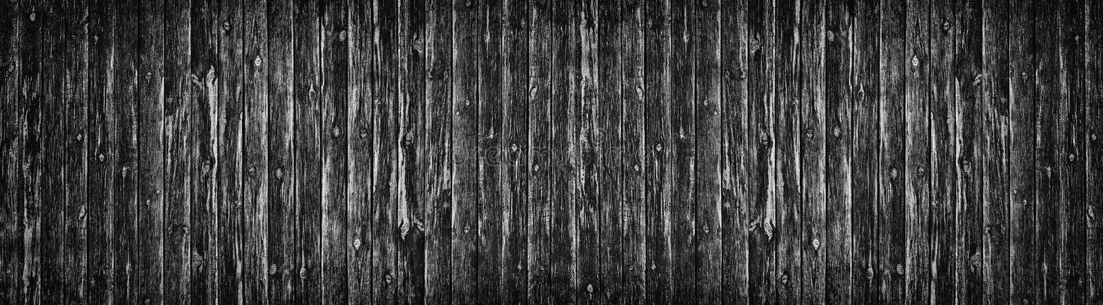 Wide old black knotty wood texture. Dark plank rough surface. Wooden board panoramic background stock image