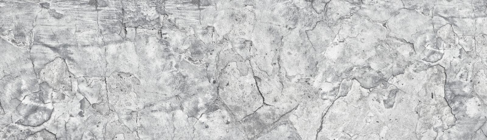 Wide old light grey shabby concrete wall. Broken cement surface texture panorama. Long grunge vintage background. Wide old light gray shabby concrete wall stock photo
