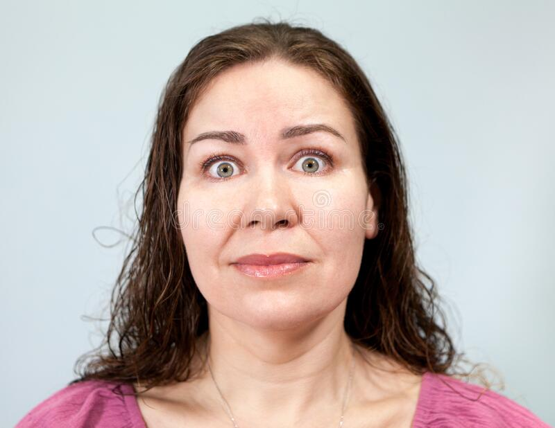 Wide-open eyes and a tense neck with fright in an adult woman, portrait on grey background, emotions series. Wide-open eyes and a tense neck with fright in an stock photos