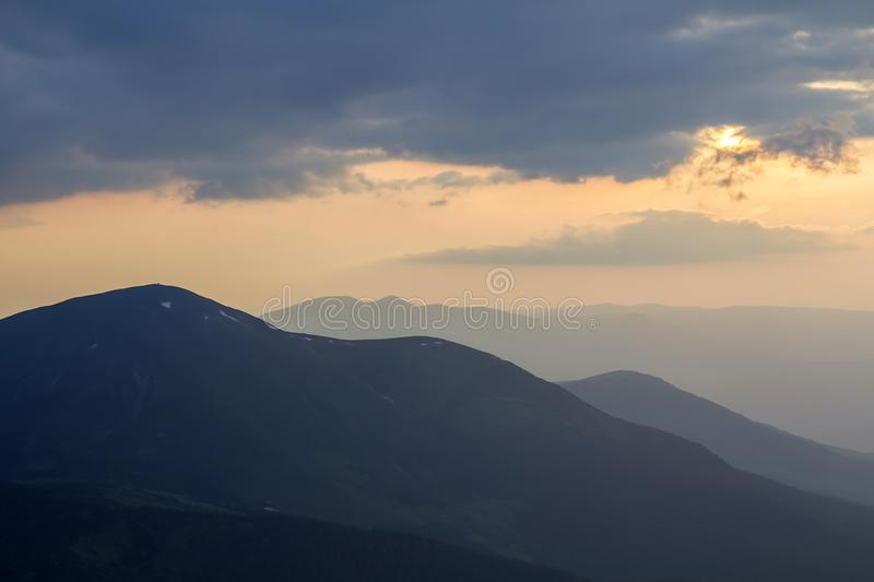 Wide panorama, fantastic view of covered with morning mist green Carpathian mountains at dawn under dark clouds and light pink sky royalty free stock image