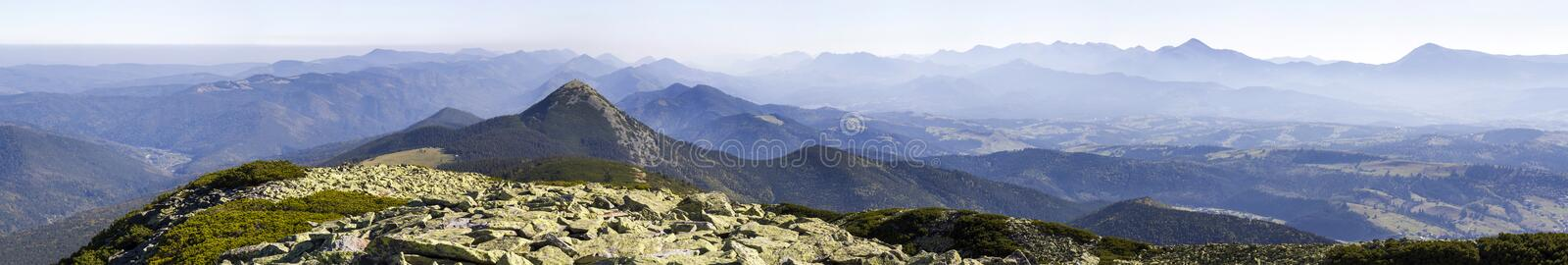Wide panorama of green mountain hills in sunny clear weather. Carpathian mountains landscape in summer. View of rocky peaks covere royalty free stock photos