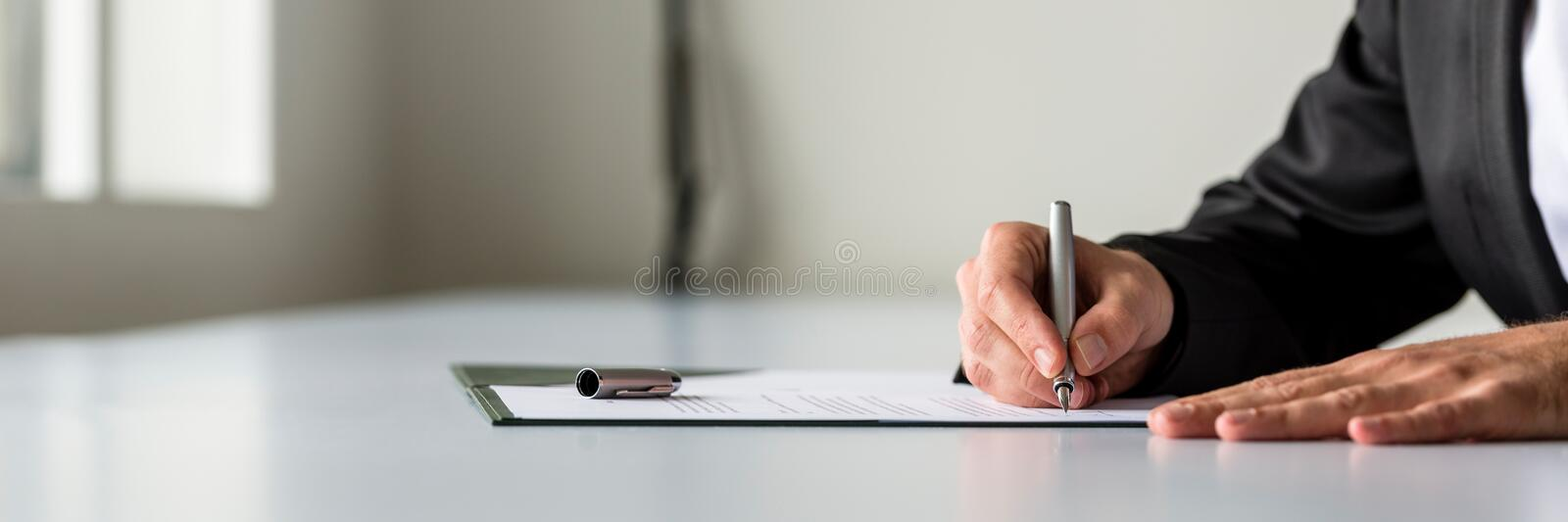 Wide panorama view of businessman hand signing legal or insurance document royalty free stock photography