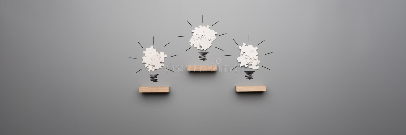 Wide panorama view of three light bulb formed by white puzzle pi stock photography