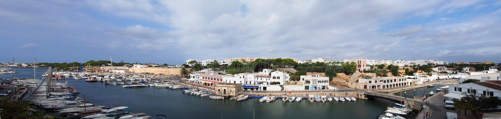 A wide panorama view of the town of ciutadella in menorca showing boats moored along the canal and surrounding buildings stock photo