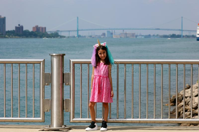 Beautiful little girl at Detroit Michigan, high definition picture of the Ambassador bridge between USA and Canada stock photo