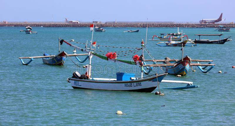 Beautiful picture of fishing boats at Jimbaran Bay at Bali Indonesia, beach, ocean, fishing boats and airport in photo. royalty free stock photo