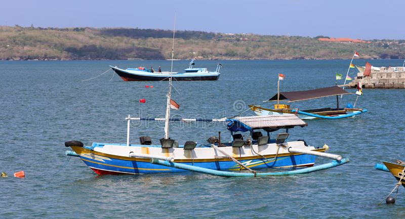Beautiful picture of fishing boats at Jimbaran Bay at Bali Indonesia, beach, ocean, fishing boats and airport in photo. Wide panoramic picture of Jimbaran Bay royalty free stock photo