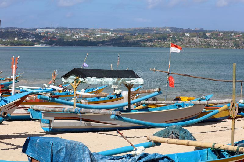 Beautiful picture of fishing boats at Jimbaran Bay at Bali Indonesia, beach, ocean, fishing boats and airport in photo. Wide panoramic picture of Jimbaran Bay royalty free stock images