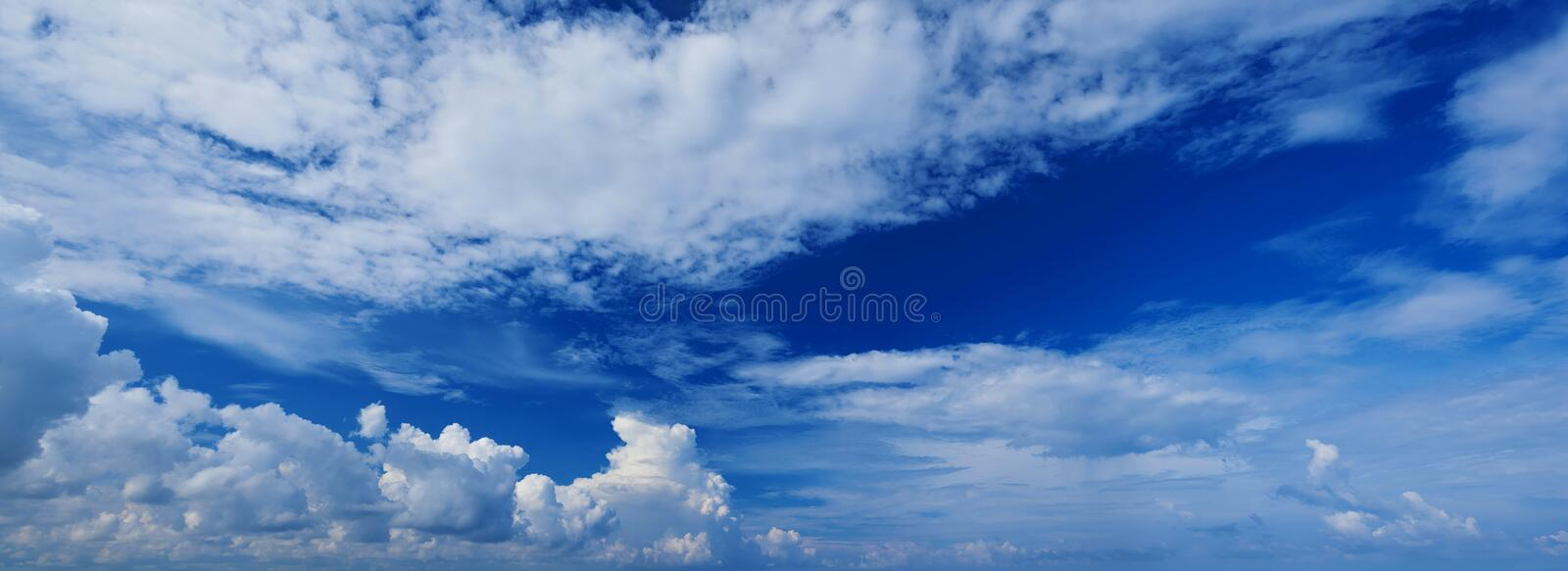 Wide panoramic view of romantic navy blue sky with white grey clouds. High resolution artistic skyline background image. Sky panor royalty free stock images