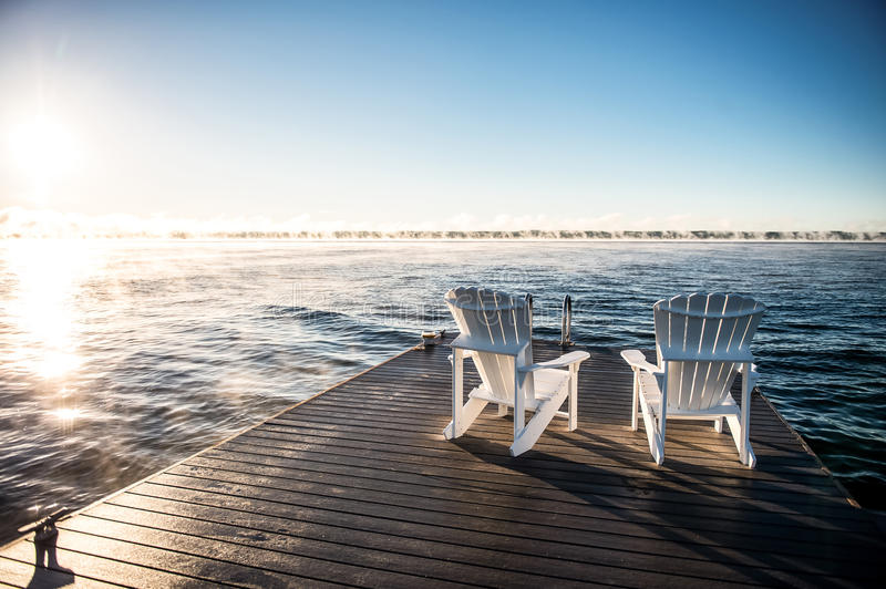 Wide photo of Muskoka Chairs on a dock with sun rising and mist. A morning sunrise rising over a dock on a blue lake Huron on Georgian Bay with 2 Muskoka chairs royalty free stock images