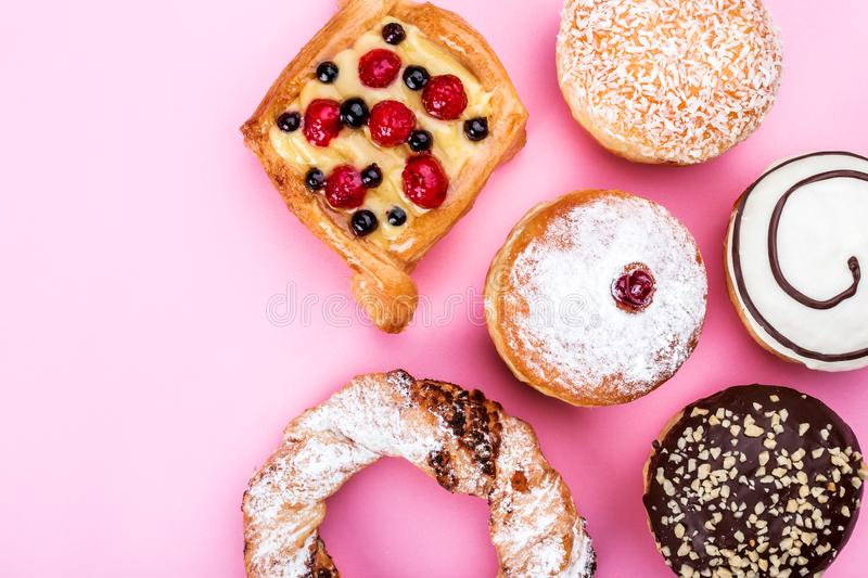 A wide range of pastry cakes, donuts, pretzels, pink, sweets, top view stock image