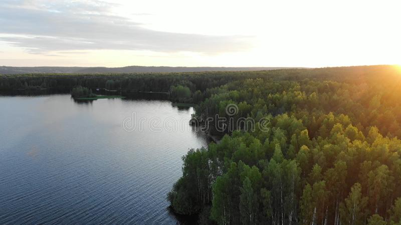 Wide river bank with sandy beach at forest in morning. Wide river bank with sandy beach at green endless forests against rising sun in morning aerial view royalty free stock photos