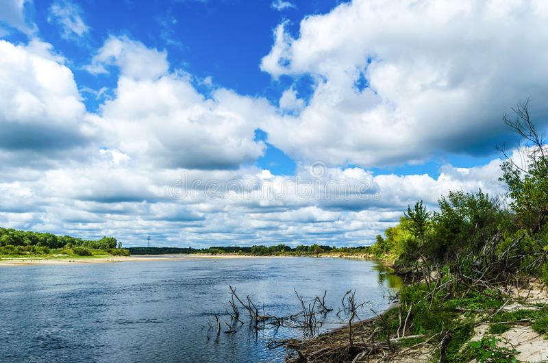 A wide river flows along a diagonal bank with a forest under an incredibly beautiful blue sky with large clouds that are reflected. In the water. Belarusian stock photography
