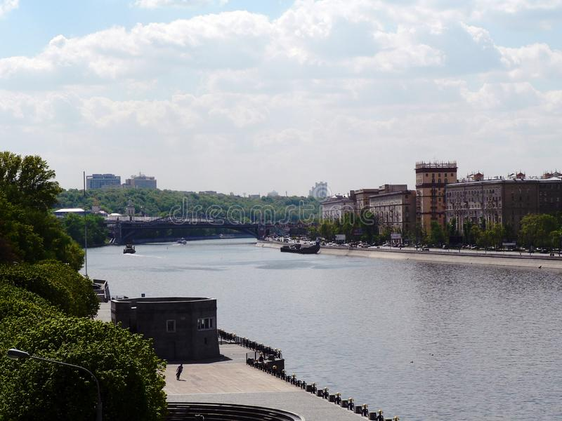 Wide river in Moscow. On the shore is a tall building. People walk on the embankment royalty free stock images