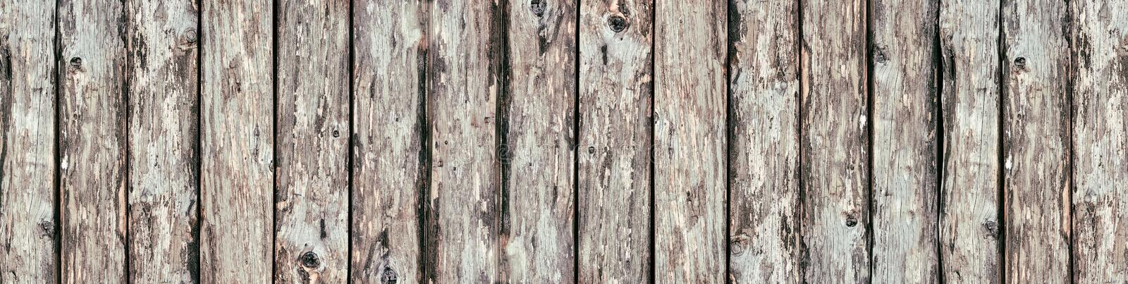 Wide rustic wood logs background - old wooden boards panorama. Wide rustic background. Rough wooden boards texture. Old knotty wood logs surface panorama stock photo