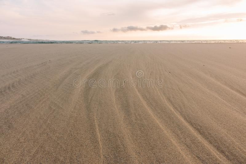 Wide sandy beach while outflow. Atlantic Ocean beach on sunset. Marine lanscape. Scenic sand beach in evening. stock photos