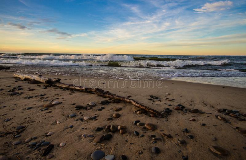 Sunset Beach With Waves On Lake Superior In Michigan. Wide sandy beach with waves crashing on the shore at Whitefish Point on the coast of Lake Superior. Wide stock images