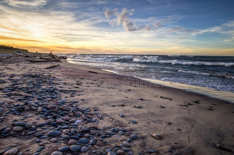Rocky Lake Superior Beach Sunset Horizon. Wide sandy beach with waves crashing on the shore at Whitefish Point on the coast of Lake Superior. Wide angle with royalty free stock image