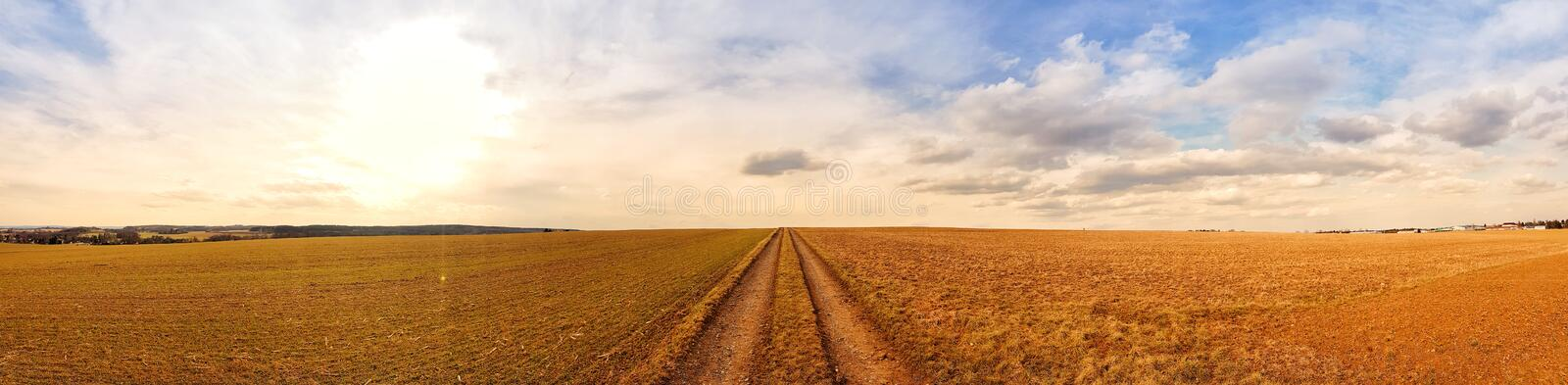 Scenic panorama view of natural landscape under a cloudy sky. Wide scenic view of landscape panorama under a cloudy sky in the nature with grass and trees stock photo
