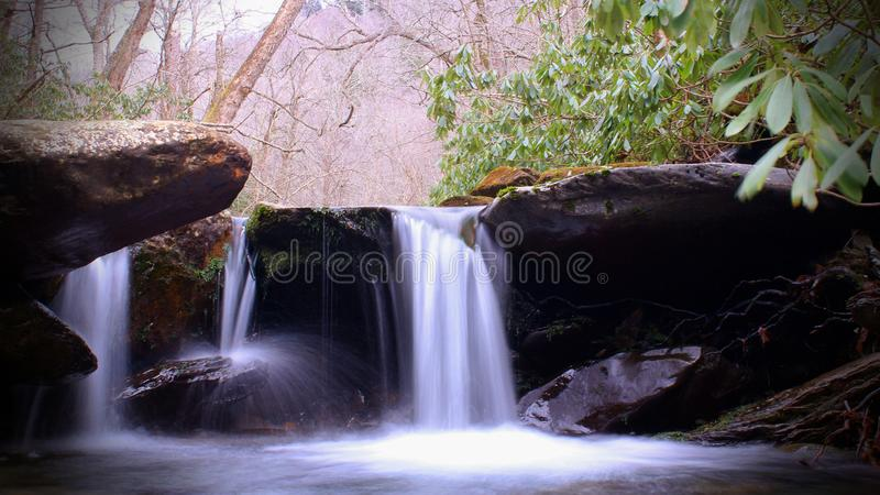 Wide Screen Photo of Waterfall in the Woods Slow Shutter Speed Motion Blurred stock images