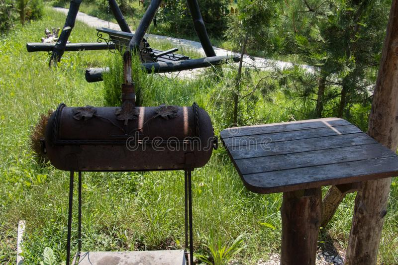 Wide shot of a barbecue grill near a table in the park and a swing on the background stock photography