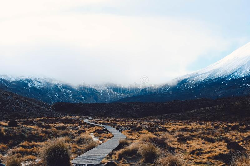 Wide shot of beautiful snowy mountains and hills and a dry desert field. A wide shot of beautiful snowy mountains and hills and a dry desert field royalty free stock image