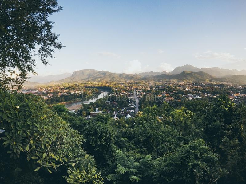 Wide shot of a city with a lake surrounded by trees in forests and mountains under a clear blue sky stock photo