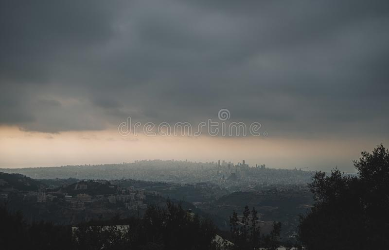 Wide shot of city surrounded with trees and mountains under a dusky sky stock photos