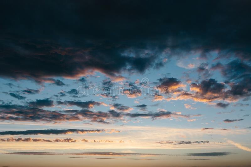 Wide shot of a cloudy sky at sunset. Cloudy sky at sunset colored in pink royalty free stock photos