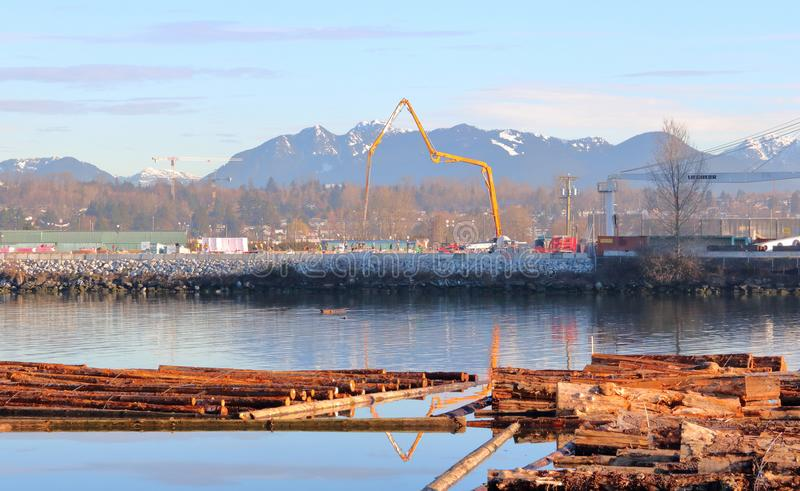 Vancouver Construction on Fraser River. Wide shot of crews pouring cement during a riverfront construction project along Vancouver, Canada`s Fraser River on stock photography
