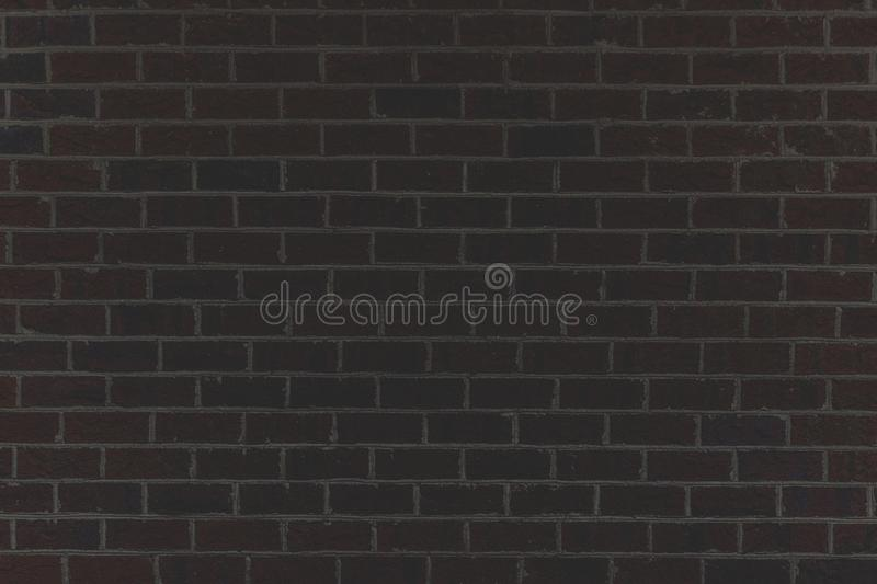 A dark colored brick wall. A wide shot of a dark colored brick royalty free stock photography