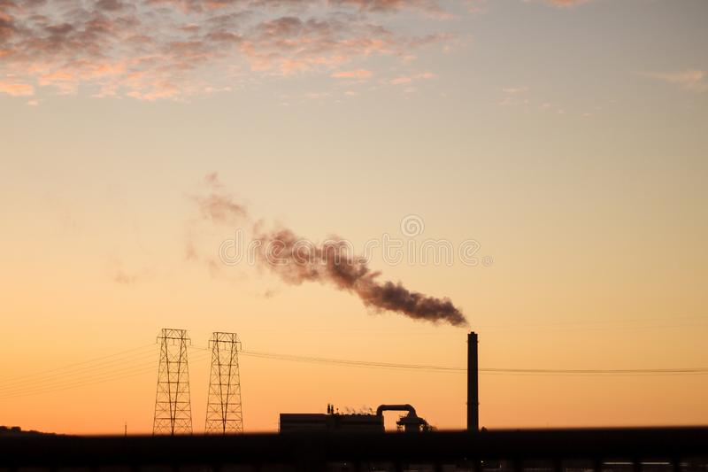 Wide shot of a factory with smoke coming out of a tall pipe - global warming. A wide shot of a factory with smoke coming out of a tall pipe - global warming royalty free stock photography