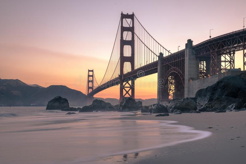 Wide shot of the Golden Gate bridge near body of water during sunset in San Francisco, California. A wide shot of the Golden Gate bridge near body of water stock image