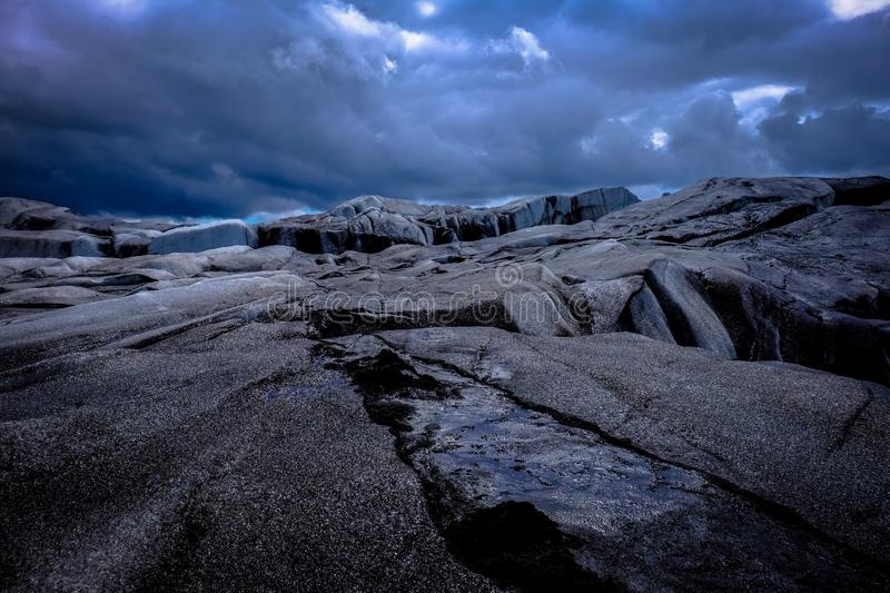 Wide shot of gray rocky surface under a cloudy sky. A wide shot of gray rocky surface under a cloudy sky royalty free stock photography