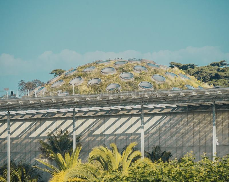 Wide shot of a greenhouse surrounded with plants under a blue sky stock photo