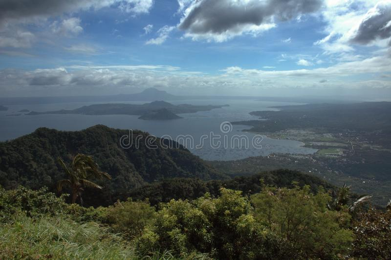 Wide shot of hills covered with green plants by the sea under a blue sky with clouds. A wide shot of hills covered with green plants by the sea under a blue sky stock photos