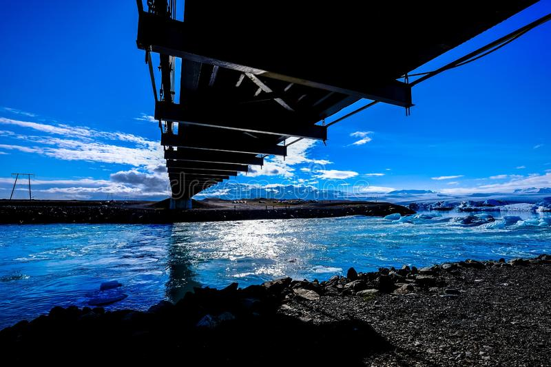 Wide shot of iced sea with ice shards and cubes under a black bridge. A wide shot of iced sea with ice shards and cubes under a black bridge royalty free stock image