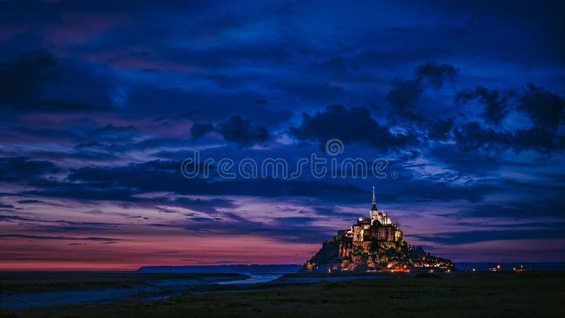Wide shot of an illuminated castle in the distance with amazing blue clouds in the sky royalty free stock photo